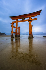 Itsukushima Shrine Low Tide (ErikFromCanada) Tags: travel blue sky orange reflection wet beautiful beauty rain japan architecture clouds dark landscape island japanese reflecting sand kyoto gate shrine stream gloomy tide low dramatic floating overcast wideangle stormy structure unesco worldheritagesite hiroshima itsukushimashrine lowtide nationaltreasure darkclouds drizzle itsukushima toriigate lightrain floatinggate a7r floatingtoriigate itsukushimashrinelowtide