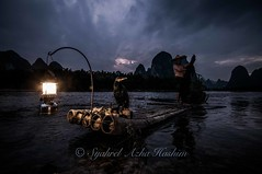 Getting dark... (Syahrel Azha Hashim) Tags: china travel light shadow vacation portrait mountain holiday detail colors hat birds clouds river cormorants dark nikon colorful dof fishermen guilin getaway unique traditional details chinese paddle naturallight scene bamboo tokina portraiture handheld bluehour lantern shallow simple dramaticsky 11mm humaninterest bambooraft traditionalclothing ultrawideangle singleexposure d300s syahrel