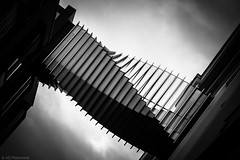 Umbilical (Anthony Plancherel) Tags: street city uk greatbritain travel bridge england sky blackandwhite bw abstract london english tourism geometric monochrome lines architecture modern canon buildings dark grey construction pattern darkness unitedkingdom britain geometry capital shapes streetphotography twist places structure diagonal walkway repetition link british minimalism shape miscellaneous minimalist modernarchitecture span offices concertina shapely modernity whiteandblack twisting greyclouds floralstreet travelphotography capitalcity repeatedpattern nearcoventgarden canon1585mm canon70d