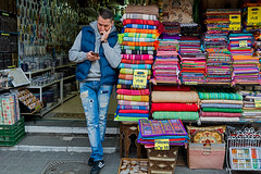 Business is low, texting is high (Poupetta) Tags: candid seller yaffo