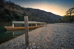 Boats at Shore (ErikFromCanada) Tags: trees sunset brown mountains japan river landscape boats japanese kyoto rocks angle harbour stones wide rope hills shore tied docked woodenboats longboats mountainriver a7r boatswaiting