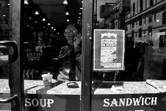 Sandwich (ATVisuals) Tags: street nyc blackandwhite food streetart reflection glass monochrome candid text soho streetphotography sandwich sidewalk elderly meal storefront deli bnw rawstreets