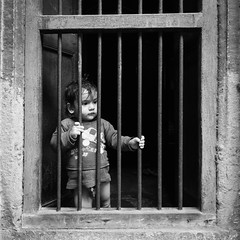 missing freedom (jaumescar) Tags: travel portrait india white black cute window look lines square grid kid space empty poor frame curious