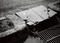 The drain in the road in cracked (Matthew Paul Argall) Tags: blackandwhite concrete 110 cement drain drainage fixedfocus 110film halinapix110f