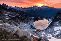 Under the Rising Sun - Hidden Lake Peak (Gabriela Fulcher Photography) Tags: red sky sun lake mountains color reflection sunrise landscape washington vivid cascades peaks northcascades hiddenlakepeaklookout
