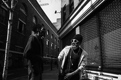 As Cool As A Cucumber (instagram.com/the_big_smoke_/) Tags: street city uk portrait england people urban blackandwhite bw black streets men london monochrome sunglasses mono cool angle britain candid afro central perspective streetphotography style streetscene scene calm streetphoto hackney capture beanie relaxed bricklane bnw peoplewatching stylish eastend streetwise urbanstreets streetstyle neckchain robmchale