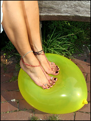 Paloma's bare feet about to pop a balloon (sunnystreets) Tags: feet female balloons outdoors foot legs balloon pop jewellery rings crushing barefoot pedicure stomping popping anklets squishing