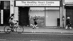 Kilburn, London 2016 (S.R.Murphy) Tags: street blackandwhite bw london monochrome bike bicycle mono cyclist outdoor pavement streetphotography walker cycle nhs runner kilburn socialdocumentary stphotographia fujix100t march2016 thehealthyheartcentre