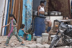 the blue water barrel (Pejasar) Tags: life family blue girls boy india wet water girl walk delhi typical waterbarrel outsidekitchen boybathing frontporchliving streetfrontproperty potsonthefire