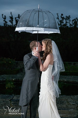 Sheltering from the rain, stealing a kiss under an umbrella. Kat and Oli's wedding day - photography and videography by Veiled Productions - wedding photography and videography Cambridgeshire