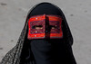 a bandari woman wearing the traditional mask called the burqa on a market, Hormozgan, Bandar Abbas, Iran (Eric Lafforgue) Tags: red portrait people woman horizontal outdoors persian clothing asia veil mask iran market muslim islam religion hijab persia headshot hidden covered iranian bazaar adults adultsonly oneperson islamic burqa ethnicity middleeastern frontview persiangulf sunni bandarabbas burka chador balouch hormozgan onewomanonly lookingatcamera burqua إيران иран embroidering 1people イラン irão straitofhormuz 伊朗 unrecognizableperson colourpicture 이란 borqe boregheh iran034i1902