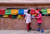 Nirmala and Khembro walk alongside the prayer flags at the Boudhanath temple in Kathmandu. (Humanity & Inclusion UK) Tags: nepal handicapinternational ngo prosthesis physiotherapy rehabilitation nepalearthquake