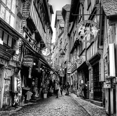 Le Mont Saint-Michel Streets (Missy Jussy) Tags: sky people bw france streets monochrome shop buildings mono souvenirs blackwhite streetphotography cobbles normandy lemontsaintmichel