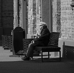 Enjoying the gentle sunlight (mkorolkov) Tags: street old city shadow blackandwhite sunlight monochrome lady bench sitting cigarette candid streetphotography fujifilm xe1 xc50230