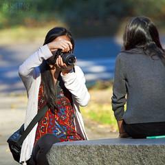 Checking Her Work (Ian Sane) Tags: park street camera portrait woman sunlight southwest oregon canon portland lens ian photography eos is photo downtown shoot photographer candid images 7d usm avenue sane ef100400mm f4556l checkingherwork