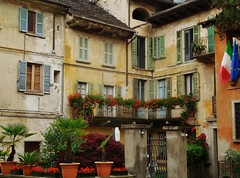 muted shades of Italy (SM Tham) Tags: flowers houses homes windows italy plants buildings garden town gate facades flags roofs shutters balconies pillars shrubs flowerpots lakeorta italianlakes planterboxes ortasangiulio