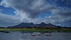 Dramatic clouds gathering over and reflecting the isle of rum, Inner Hebrides Scotland