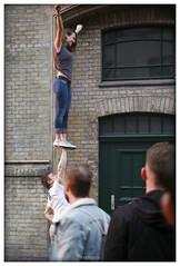 one hand lift (piktorio) Tags: sunset woman man berlin girl kreuzberg germany artists balance moment acrobats labourday partners sideway streetparty myfest piktorio firstaofmay