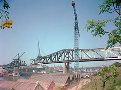 Metro Bridge nearing completion, 1978 (Tyne & Wear Archives & Museums) Tags: road city bridge roof sky abstract flower reflection tree industry water grass leaves wall buildings river landscape daylight interesting construction industrial branch unitedkingdom mark debris bridges social structure gateshead tynebridge petal cranes soil land vegetation unusual 1970s tyneside development slope newcastleupontyne fascinating digitalimage metrobridge rivertyne highlevelbridge civilengineering northeastengland northeastofengland june1978 colourphotograph turnersltd scenicviewsofnewcastle