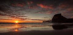Piha Paradiso (zebedee1971) Tags: ocean sunset sea sky orange reflection beach nature rock clouds landscape sand rocks surf waves glow natural dusk hill calm hills serene brilliant piha