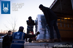 Islamic Relief USA staff and volunteers unload a truck of water bottle to distribute into 10 smaller trucks.