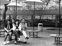 Convergence (Andy WXx2009) Tags: china street family girls urban blackandwhite men monochrome fashion umbrella table outdoors hongkong women asia sitting artistic candid femme streetphotography style meeting brunette crosslegged asiangirls
