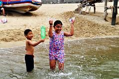 Getting wet (Roving I) Tags: girls sea playing boys wet water siblings spray vietnam beaches danang splashing plasticbottles brothersandsisters sontra