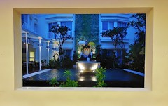 a picture window (SM Tham) Tags: trees windows bali plants building wall indonesia island hotel cafe pond shrine terrace landscaping courtyard frame bluehour fountains waterfeature umbrellas shrubs kuta parasols picturewindow landscapedesign holidayinnexpress kutasquare