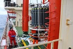 Eine Rosette mit ringförmig angeordneten Flaschen wird nach der Probenname wieder an Bord verstaut. Die Flaschen wurden in verschiedenen Tiefen mit Wasser gefüllt, das später in Laboratorien analysiert werden wird.