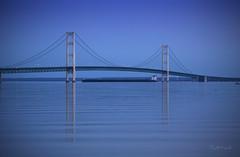 The Mackinac Bridge & The Great Lakes Freighter (Stella_Kar) Tags: blue lake nature architecture reflections landscape lights evening ship pastel upperpeninsula impressive mackinacbridge saintignace greatlakesfreighter mightymac