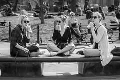 Sippy Cup (John St John Photography) Tags: newyorkcity blackandwhite bw newyork sunglasses bench sitting cross outdoor washingtonsquarepark watching streetphotography drinks sipping greenwichvillage youngwomen candidphotography crosslegged