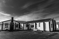 Abandoned Huts (Howie Mudge LRPS) Tags: wood old uk travel windows roof sky blackandwhite bw building travelling tower abandoned monochrome tarmac wales architecture clouds outside army outdoors mono blackwhite nikon day doors bright empty cymru sunny structure hut d750 disused fullframe accommodation polarizer gwynedd polariser tywyn 24120mmf4vr