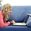 Woman with headset and laptop. (acespace) Tags: pink blue light woman home girl smile female computer notebook person one pc education chat pretty technology adult laptop room young talk headset couch communication sofa blond rest network lying typing speak headphone divan laying caucasian communicative