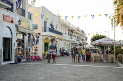 Paros - near the port (kutruvis nick) Tags: travelling architecture buildings island greek nikon chairs hellas flags greece tables shops balconies labels nik merchandise umbrellas vacations paros peopl pavedroad d5100 kutruvis