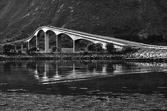 an architecture as challenging as the landscape surrounding it (lunaryuna (off to Iceland for 2 weeks)) Tags: bridge bw mountain mountains water monochrome norway architecture reflections blackwhite fjord ripples lunaryuna thenorth lofotenislands distortions seastrait gimsoystraumenbru