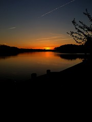 Sunset over the Water (emtay15) Tags: trees orange plants sun lake reflection nature water clouds river outdoors dock horizon treeline