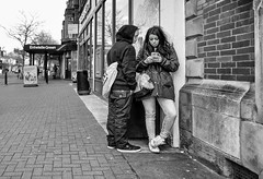 I was a teenage text addict (streetstory [is offline]) Tags: uk england people tree reflections hoodie 28mm streetphotography sneakers lancashire jeans ricohgr texting teenagecouple inexplore march2016