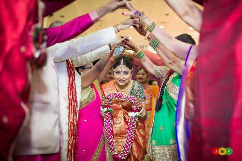 A gujrati tradition: Bride walks through the aisle of hands to welcome her groom with garlands.