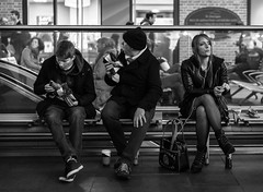 Distracted (Cliff.j) Tags: life street city people urban london public glass girl look hat station leather night contrast zeiss scarf bench bag waiting dof looking cross boots eating candid seat sony father watching group strangers style railway son indoor scene kings jacket carl round pastry headphones fishnets inside unposed glance a7 turning bobble holdall mirrorless