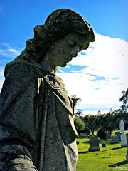 Guardian Watch Over Thee (BenitaMarquez) Tags: blue shadow sky white green face cemetery grave grass statue stone angel clouds death cross headstone