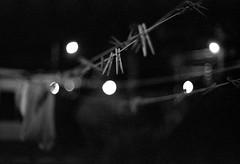 Clothesline Bokeh (Ca$hreno) Tags: nightphotography blackandwhite film monochrome night blurry nikon tmax3200 dof kodak bokeh availablelight ishootfilm epson filmcamera grainy nikonf3 f12 closeline shallowdof normallens filmphotography v700 50mmf12ais