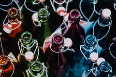 Colorful Bottles (freyavev) Tags: pink blue orange green germany bayern deutschland bavaria 50mm bottle colorful bottles nuremberg grain depthoffield repetition brightcolors butlers nürnberg openbottles