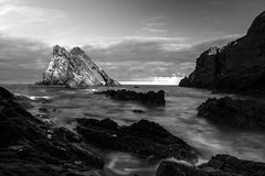 Bow Fiddle Rock, lit up by sunset in long exposure black & white, Portknockie, Moray, Scotland (grumpybaldprof) Tags: uk sea bw seagulls detail water monochrome birds rock port scotland blackwhite sandstone waves arch harbour tourist stack bow fiddle quartz milky moray gleaming nesting portknockie northsea bowfiddlerock naturalseaarch