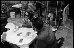 (The First Bite) (Robbie McIntosh) Tags: leica girls blackandwhite bw woman film monochrome analog 35mm eyecontact candid burger strangers streetphotography sausage rangefinder bn meat grill pork summicron negative barbecue analogue wurst streetfood m2 ilford fp4 biancoenero argentique leicam2 fingerfood dyi selfdeveloped ilfordfp4 pellicola analogico sunny16 nometering leicam filmisnotdead autaut leicasummicron35mmf20iv guessexposure summicron35mmf20iv leicasummicron35mmf2i internationalstreetfoodfestival arsimagofd arsimagofddeveloper