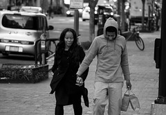 A Couple on 6th St. NW (John Bense) Tags: street city people urban blackandwhite love boyfriend monochrome smile shopping washingtondc hands girlfriend chinatown galleryplace holdhands