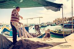 The Fisherman (Chiara Salvadori) Tags: travel sea sun fish seascape colors island spring fishing fisherman mediterranean village market harbour outdoor ships culture malta traveling tradition freetime gozo marsaxlokk luzzi