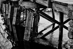 Support system (trochford) Tags: wood bridge blackandwhite bw usa reflection texture geometric water monochrome stone canon river ma mono pier blackwhite support exterior outdoor massachusetts newengland pile rippled concord piling woodgrain glassy abutment crossbeam concordriver oldnorthbridge