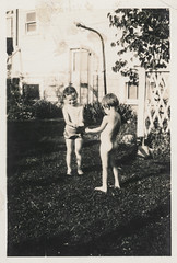 Two children showering in the back yard (simpleinsomnia) Tags: old white black monochrome yard vintage naked nude found outside shower blackwhite back kid backyard child antique snapshot photograph vernacular foundphotograph