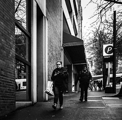 Walking Down The Street (TMimages PDX) Tags: road street city people urban blackandwhite monochrome buildings portland geotagged photography photo image streetphotography streetscene sidewalk photograph pedestrians pacificnorthwest avenue vignette fineartphotography iphoneography