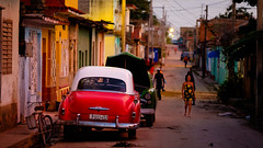 Evening Light on Classic 1950s American cars in Trinidad, Cuba (justinclayton99) Tags: road street blue sunset red orange woman color colour green classic car bike bicycle yellow lady trash walking lights evening cu fuji dress cuba wires cycle 1950s rubbish trinidad tropical fujifilm caribbean xt1 sanctispritus